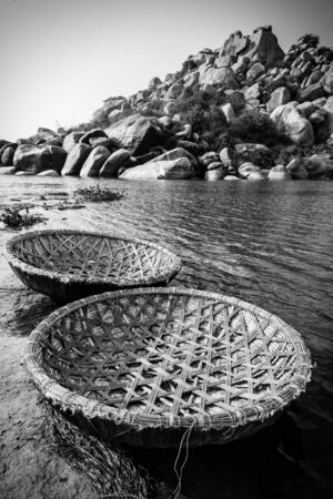 Traditional rural coracle boats on Tungabhadra river in Hampi in black and white.