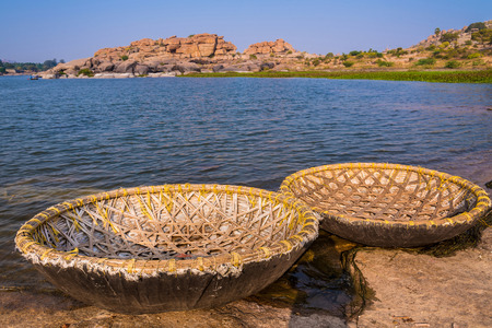Rural coracle boats waiting for passengers on Tungabhadra river bank in Hampi, India.