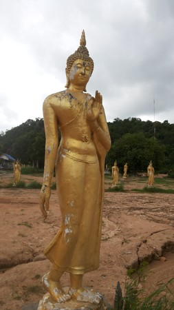 left hand: Buddha golden yellow Sitting in an elegant manner. His smiling face Dissuade the left hand raised Body attached to the left hand Gautama Buddha traces paint cracked out on time.