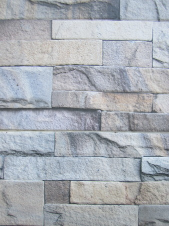 Wall made from sandstone bricks as concatenation. The stone was cut into pieces with different color, different size wall is very beautiful.