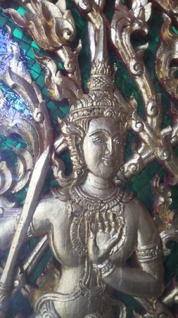 hand guard: Four-arm gods, wooden carvings and delicate. Beautifully carved Guard the church door sword in his hand, body jewelry precious sapphire diamond. Stock Photo