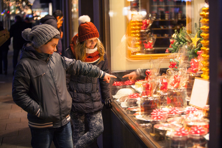 christmas motive: Children stood before the shop-window with a Christmas motive and point at the presents Stock Photo