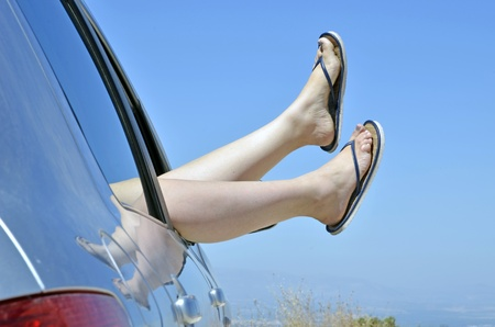 Woman with feet in the way the car window on vacation. Concept of happiness and relaxation during the trip in the summer photo