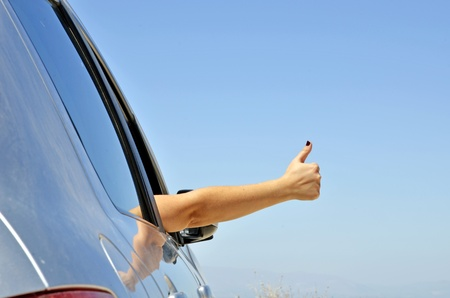 the car window: young hand gesture ok with the car window. Symbol that all is well for holiday travel