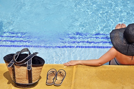 Women with pamela in a relaxed position in the pool with bag and sandals  photo