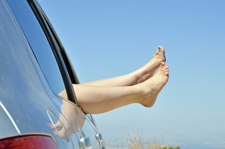 women with bare feet out the window of the car road on vacation. Concept of happiness and relaxation during the trip in the summer photo
