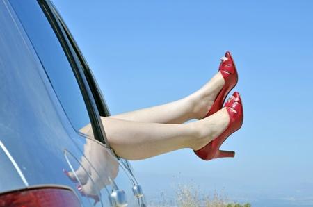 piernas con tacones: mujer con rojo zapatos por cierto la ventana del coche de vacaciones. Concepto de felicidad y diversi�n durante el viaje en el verano