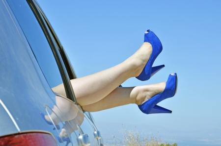 foot fetish: woman with blue shoes by the way the car window on vacation. Concept of happiness and fun during the trip in the summer  Stock Photo