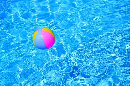 Pelota de playa multicolor en la piscina