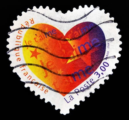 FRANCE - CIRCA 2003: A Heart Shaped Stamp with the word love you in French, circa 2003 photo