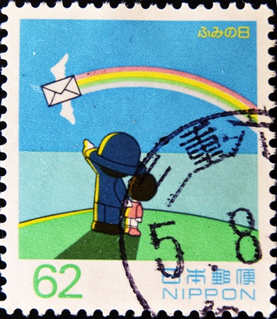 JAPAN - CIRCA 1990: A stamp printed in Japan showing a boy and a postal worker who see a letter on a rainbow, circa 1990  photo