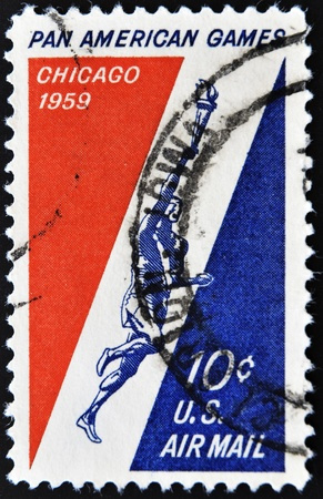 UNITED STATES OF AMERICA - CIRCA 1959: A stamp printed in USA shows athlete with the Olympic flame, the start of the pan american Games in Chicago, circa 1959  photo