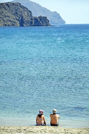 Couple sitting back on the beach. Natural Park Cabo de Gata photo