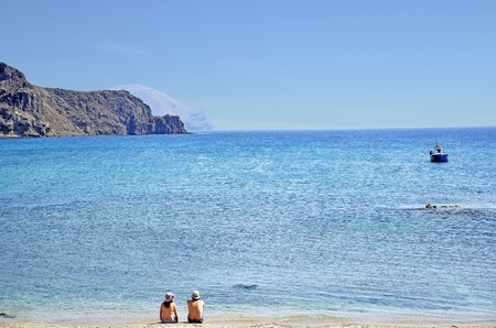 Couple sitting back on the beach. Natural Park Cabo de Gata photo