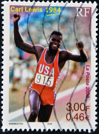 FRANCE - CIRCA 2000: A stamp printed in France shows Carl Lewis, 1984, circa 2000 Stock Photo - 11139859