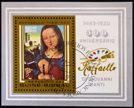 GUINEA BISSAU - CIRCA 1983: A stamp printed in Guinea Bissau shows a picture of the Virgin Mary and baby Jesus painted by Raphael, circa 1983 photo