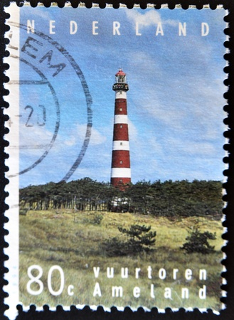 HOLLAND - CIRCA 1995: A stamp printed in Holland shows lighthouse at the island Ameland, circa 1995 photo