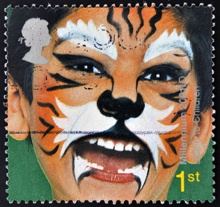 UNITED KINGDOM - CIRCA 2001: A stamp printed in England, is dedicated to painted faces of children, Tiger, circa 2001 Stock Photo - 11099044