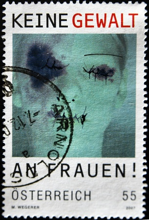 nonviolence: AUSTRIA - CIRCA 2008: A stamp printed in Austria shows a face of a woman with cuts and bruises under the banner of non-violence against women, circa 2008  Stock Photo