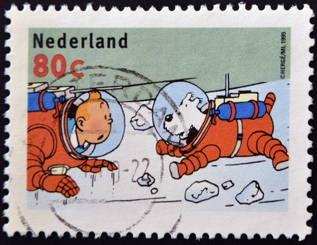 cancelled stamp: NETHERLANDS - CIRCA 1999: A stamp printed in Holland, shows an illustration of the book Explorers on the Moon with Tintin, Snowy in space suits, circa 1999