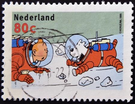 """philatelist: NIEDERLANDE - CIRCA 1999: Ein Stempel in Holland gedruckt, zeigt eine Darstellung des Buches """"Schritte auf dem Mond"""" mit Tim, Struppi in Raumanz�gen, ca. 1999"""