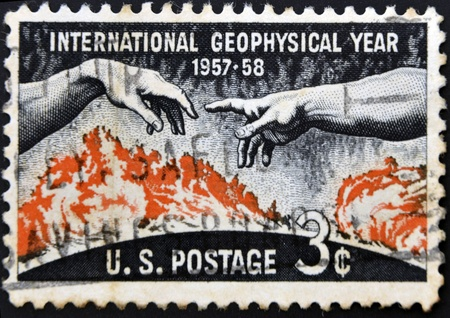 UNITED STATES OF AMERICA - CIRCA 1958: A stamp printed in the USA shows Solar disc and hands from Michelangelo�s Creation of Adam, International Geophysical year 1957-58, circa 1958 photo