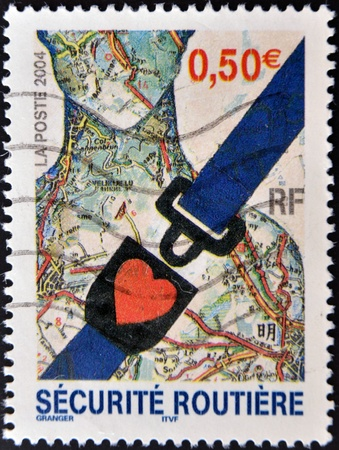 FRANCE - CIRCA 2004: A stamp printed in France dedicated to safety in the car, and shows a seat belt, circa 2004 photo