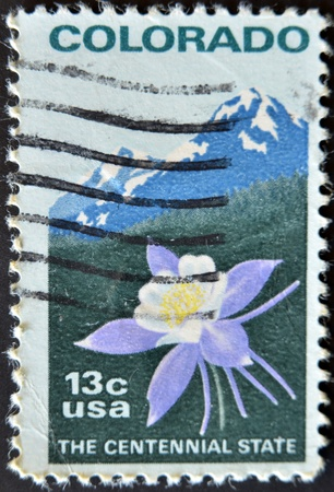 UNITED STATES OF AMERICA - CIRCA 1977 : stamp printed in USA, shows Colombine flower and Rocky Mountain, circa 1977  photo