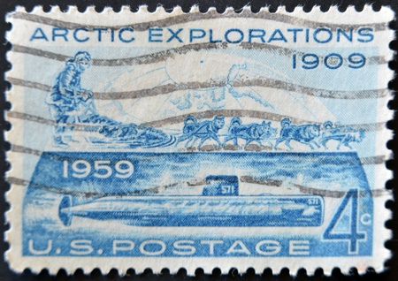 UNITED STATES OF AMERICA - CIRCA 1959: a stamp printed in the USA shows Conquest of the Arctic by Land by Rear Admiral Robert Edwin Peary 1909 and by sea by the submarine Nautilus in 1958, circa 1959  photo