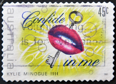 confide: AUSTRALIA - CIRCA 1994: A stamp printed in Australia dedicated to Kylie Minogue shows lips and a key referring to the song confide in me, circa 1994 Stock Photo