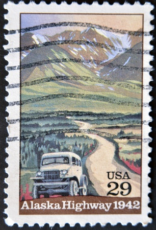 UNITED STATES OF AMERICA - CIRCA 1992: A stamp printed in USA shows Alaska Highway and the machine, circa 1992 photo