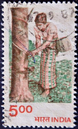 INDIA - CIRCA 1980: A stamp printed in India dedicated to crafts, shows a Women collecting rubber from a tree, circa 1980 photo