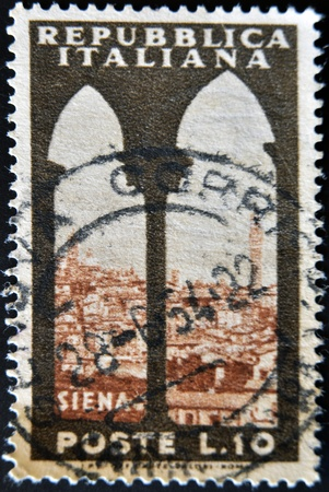 ITALY - CIRCA 1960: A stamp printed in Italy shows Siena view through the window, circa 1960 photo