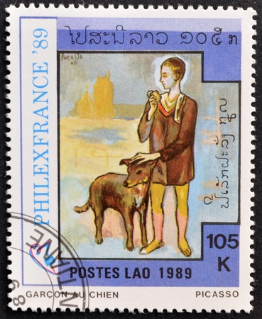 pablo picasso: LAOS-CIRCA 1989: A stamp printed in the Laos shows painting the child and the dog by Pablo Picasso, circa 1989 Editorial