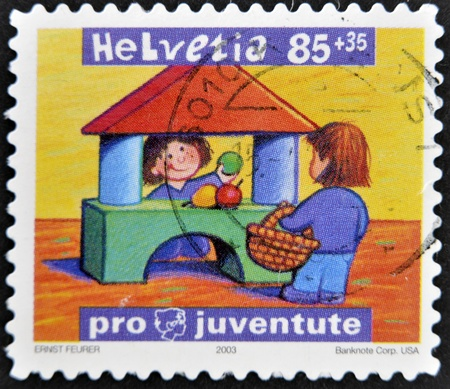 SWITZERLAND - CIRCA 2003: A stamp printed in Switzerland shows two children playing to sell fruit, circa 2003 Stock Photo - 11804010