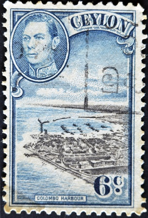 CEYLON-CIRCA 1937:A stamp printed in Ceylon shows image of The Colombo Harbour and King George VI, circa 1937  Stock Photo - 11878888