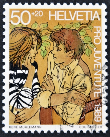 SWITZERLAND - CIRCA 1989: A stamp printed in Switzerland shows a young couple in love, circa 1989 Stock Photo - 11949454