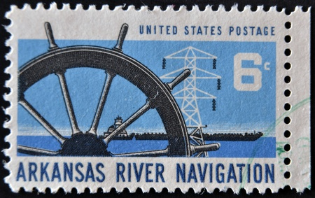 UNITED STATES - CIRCA 1968: A stamp printed in USA dedicated to arkansas river navigation, shows ship wheel, power transmission tower and barge, circa 1968   photo