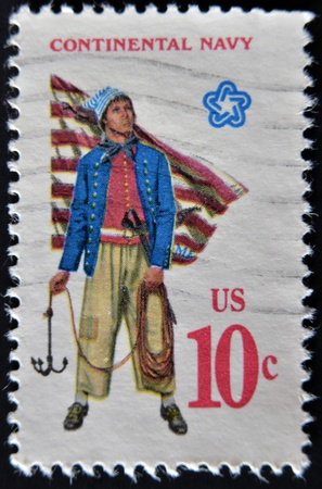 grappling: UNITED STATES - CIRCA 1970: A stamp printed in USA shows Military uniform of the American Continental Navy. Sailor with grappling hook, First Navy Jack, circa 1970