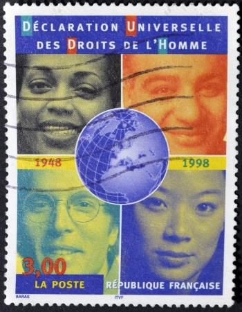 diritti umani: FRANCIA - CIRCA 1998: Un timbro stampato in Francia mostra i volti di persone di razze diverse in riferimento alla dichiarazione universale dei diritti umani, circa 1998