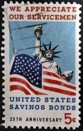 UNITED STATES OF AMERICA - CIRCA 1966: A stamp printed in USA dedicated to Honoring American servicemen and US savings bonds, shows Statue of Liberty and American Flag, circa 1966  photo