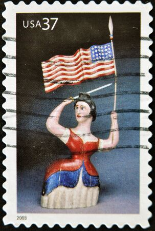 UNITED STATES OF AMERICA - CIRCA 2003: A stamp printed in USA shows woman with USA flag and sword, circa 2003 photo