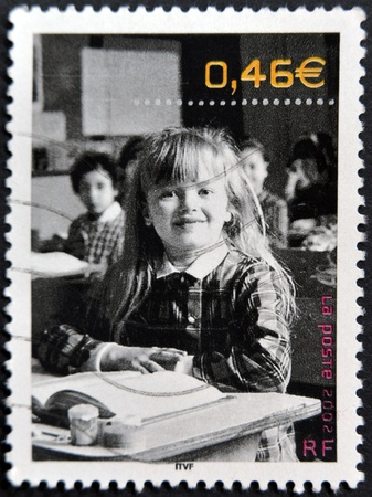 FRANCE - CIRCA 2002: A stamp printed in France shows a smiling girl in school, circa 2002  photo