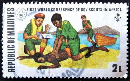 salvavidas: Islas Maldivas CIRCA 1973: sello impreso por las Islas Malldive, muestra boy scouts Salvamento y Socorrismo, alrededor del a�o 1973