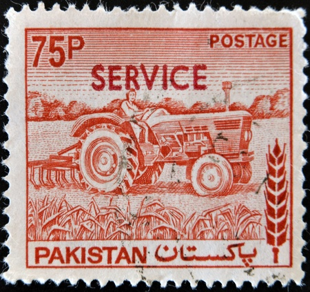 PAKISTAN - CIRCA 1970: A stamp printed in Pakistan shows woman tractor driver, circa 1970 Stock Photo - 12207517