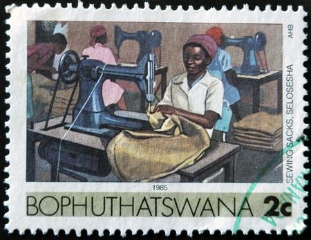 BOTSWANA - CIRCA 1985: A stamp printed in Botswana show woman sewing clothes, sewing machine, circa 1985