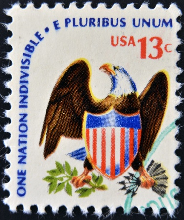e pluribus unum: USA - CIRCA 1975  A stamp printed in USA from the  Americana  issue showing an eagle and shield and the inscription  One Nation Indivisible-E Pluribus Unum , circa 1975