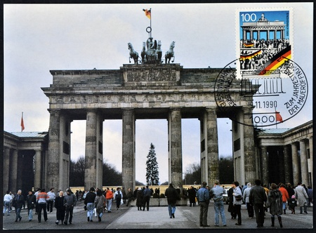 iron curtain: GERMANY - CIRCA 1990  A postcard printed in Germany commemorates the fall of the Berlin Wall on November 9, 1989, shows brandenburg gate, circa 1990