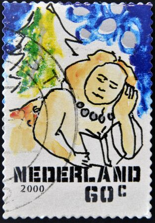 HOLLAND - CIRCA 2000  A stamp printed in Holland shows reclining woman reading, circa 2000 Stock Photo - 12965794