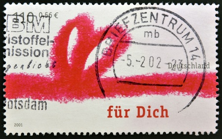 GERMANY - CIRCA 2001: A stamp printed in Germany shows drawing of a red ribbon with the words for you, circa 2001 Stock Photo - 13285846